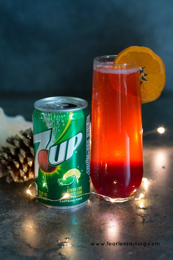 A can of 7UP next to a cranberry syrup mocktail. An orange slice is garnishing the glass.