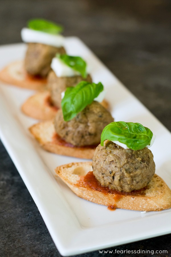 Crostini topped with marinara, a meatball, mozzarella and fresh basil
