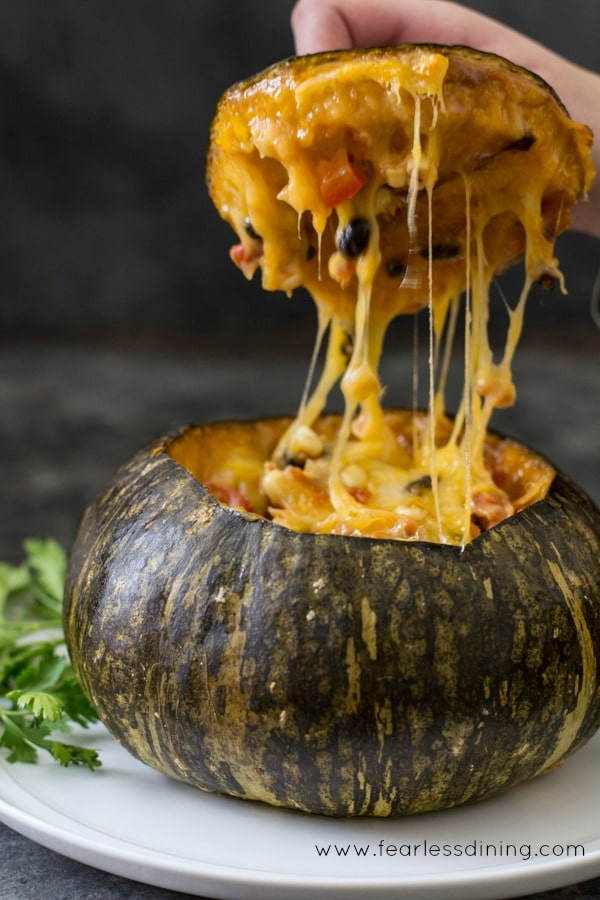 Pulling the top off a stuffed kabocha squash. Stretchy cheese is pulling between the lid and squash.