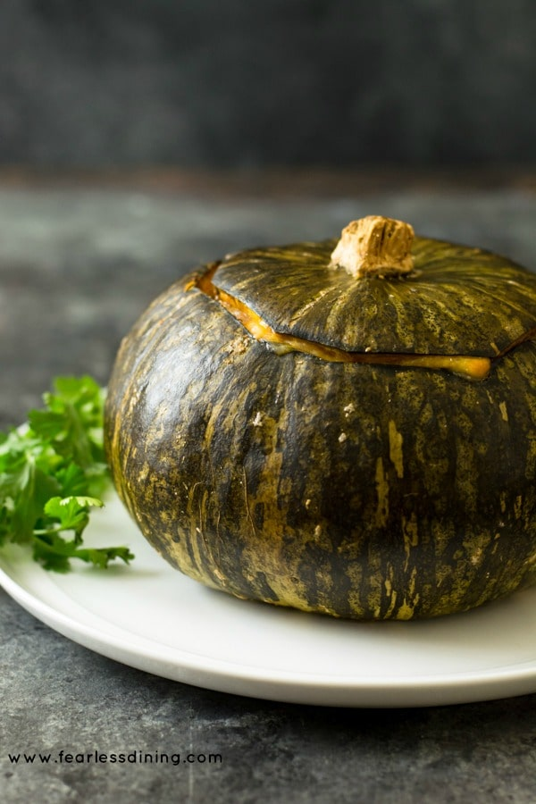 A roasted stuffed kabocha squash on a plate.