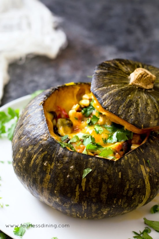 A roasted kabocha squash stuffed with corn, tomatoes, black bean, peppers, and melted cheeses.
