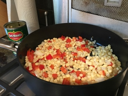 Corn, red pepper and onion cooking in a pan on the stove.
