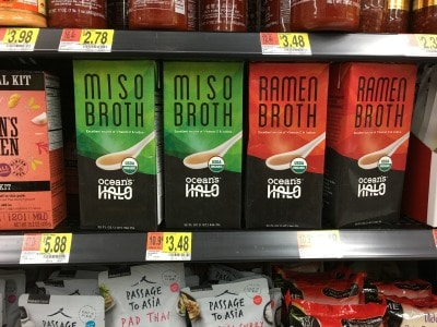 containers of miso broth on a store shelf.