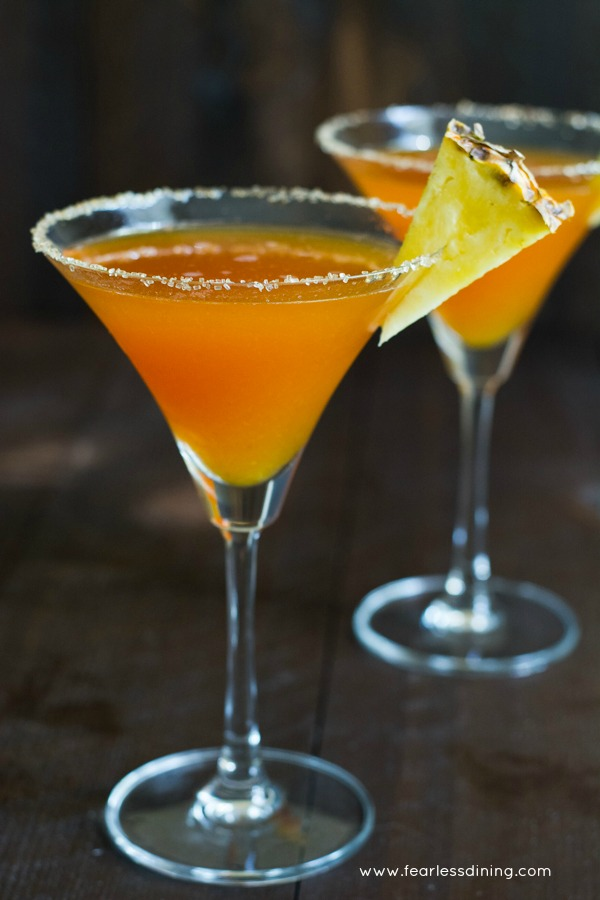 Two prickly pear margaritas in martini glasses. A slice of pineapple garnishes the glass