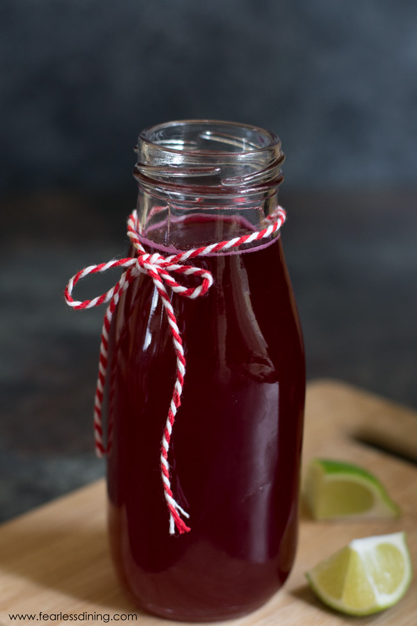 a jar of prickly pear syrup. The jar has a red and white string tied in a bow around the neck of the jar.