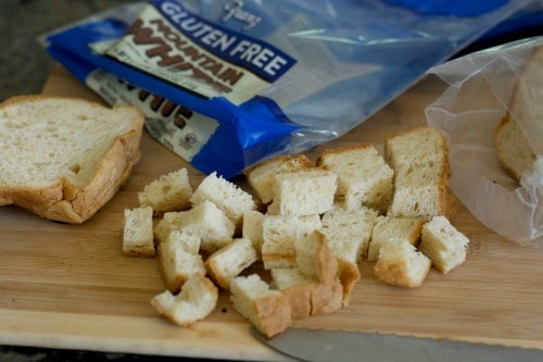 Gluten free bread chopped into cubes on a cutting board