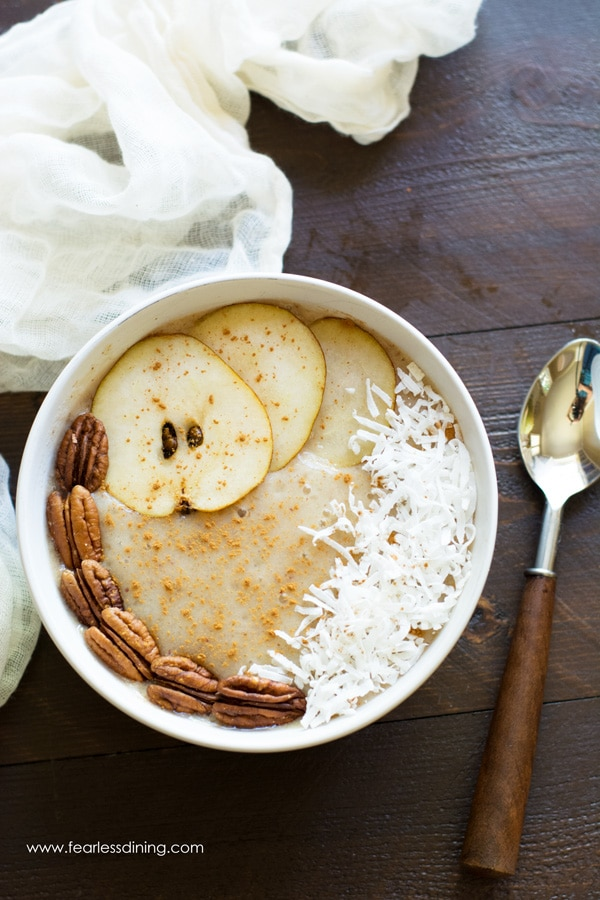 Top view of a pear smoothie bowl. There are sliced pears, pecans and coconut. A wooden handled spoon is next to the bowl.