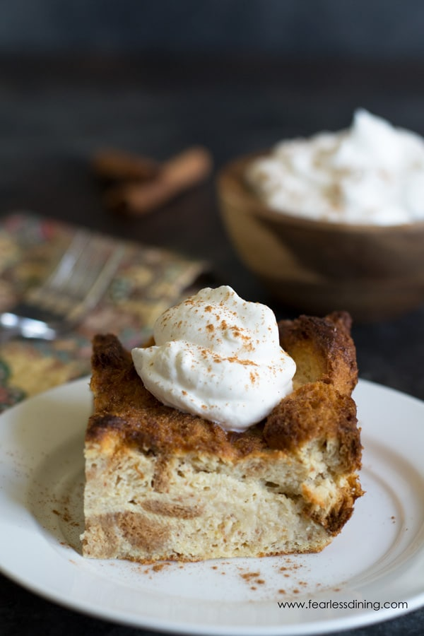 A slice of bread pudding with a dollop of whipped cream. The bowl of whipped cream is in the background.