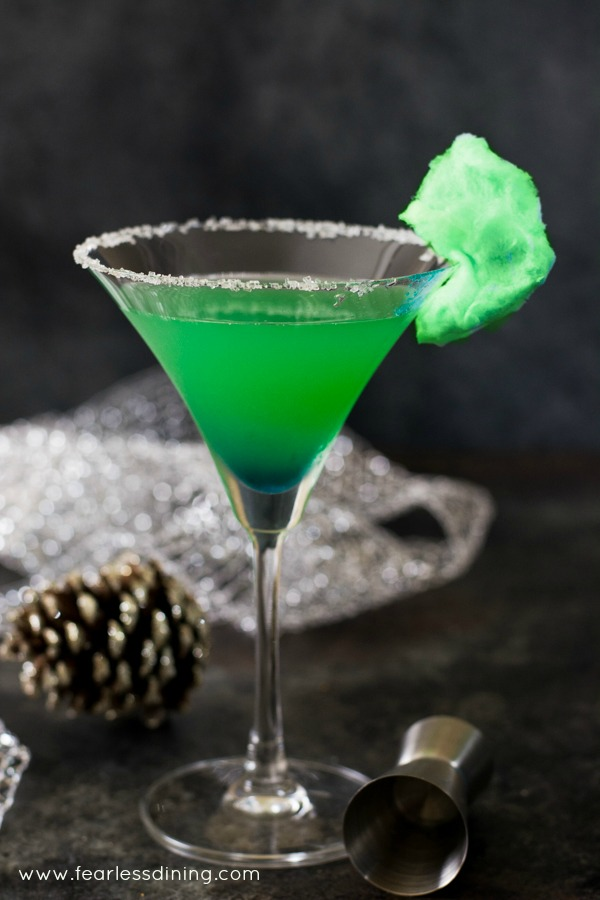 A green Grinch Vodka cocktail. Green puffy cotton candy garnishes the martini glass.