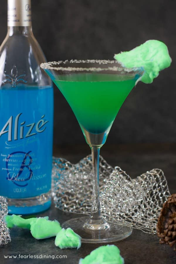 A Grinch vodka cocktail with a bottle of Alizé vodka next to the glass. Pieces of green cotton candy are in the foreground.