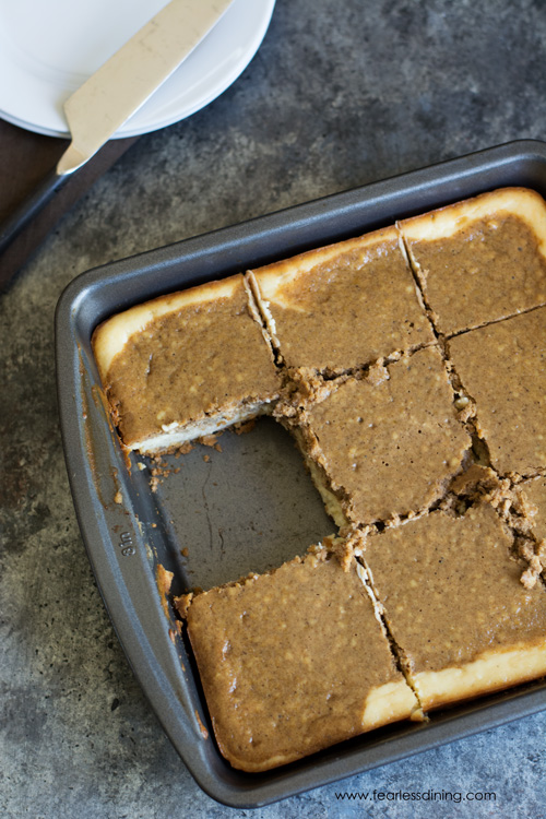 A pan of gluten free gingerbread cheesecake bars. One piece is missing