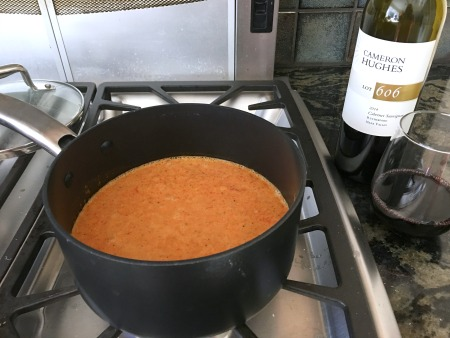 Red pepper soup cooking on the stove in a pot. A bottle of wine is next to the stove