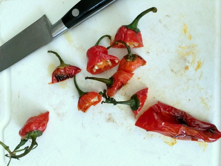 Red blistered shishito peppers on a cutting board. A few stems are next to the chopped pepper