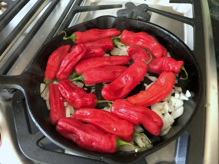 Red shishito peppers and onion cooking in a cast iron skillet