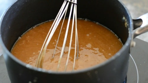 A pot of cooking toffee where the butter separated out. It looks oily.
