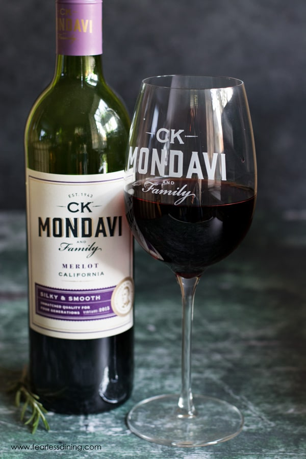 a bottle of ck mondavi merlot and a glass of wine next to the bottle