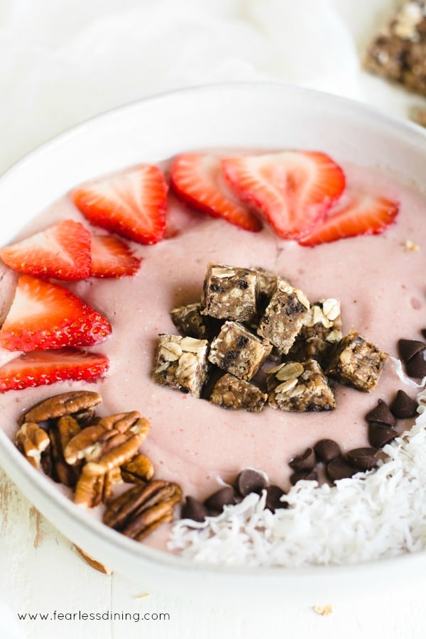 a close up of a strawberry oatmeal smoothie bowl. The bowl has fresh strawberries, pecans, and coconut on top