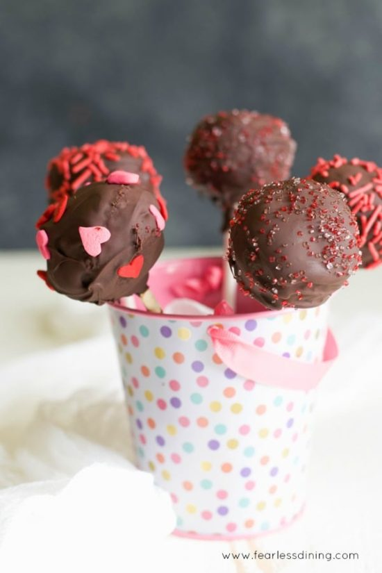 chocolate gluten free cake pops in a small pail with pastel polka dots.