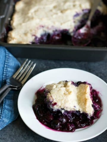 a serving of blueberry cobbler on a small white plate next to a baking dish of cobbler