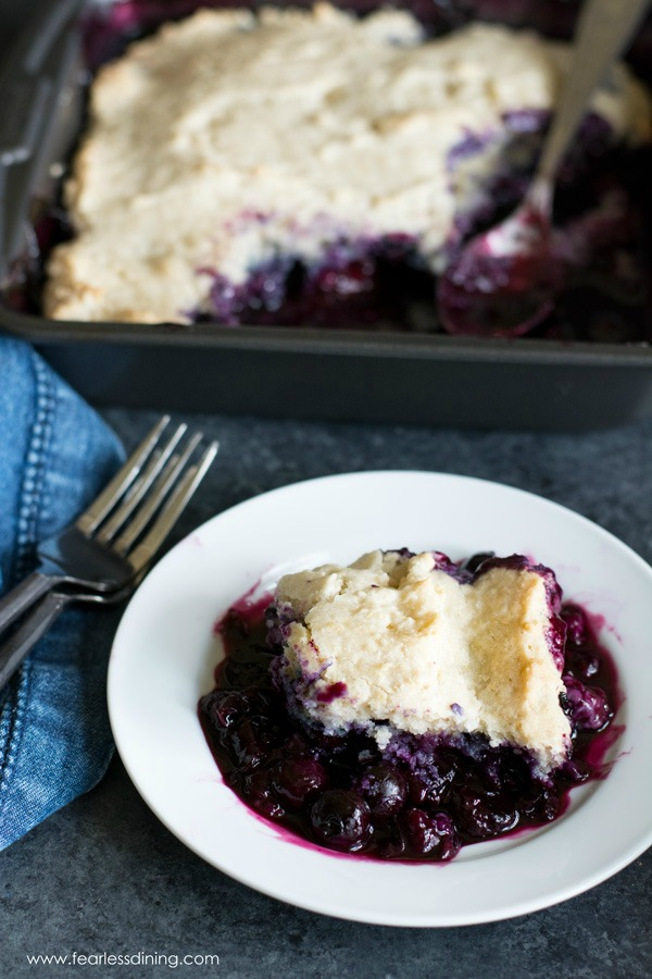 A slice of gluten free blueberry cobbler on a white plate.