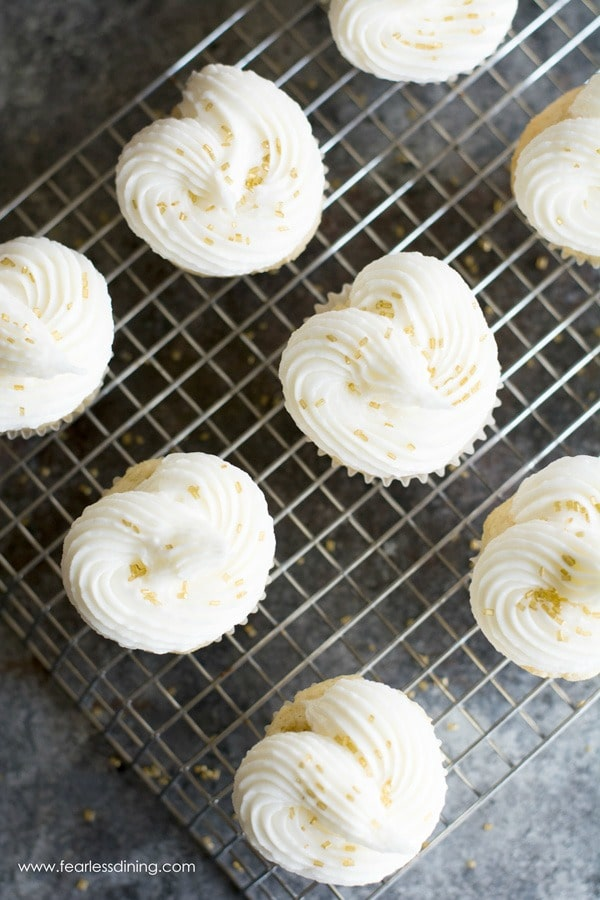 The top view of a batch of gluten free champagne cupcakes on a cooling rack. The white frosting was applied in a heart shape.