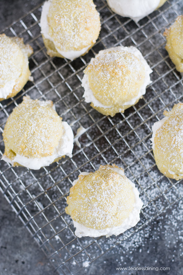 top view of gluten free cream puffs on a cooling rack. They are filled with whipped cream