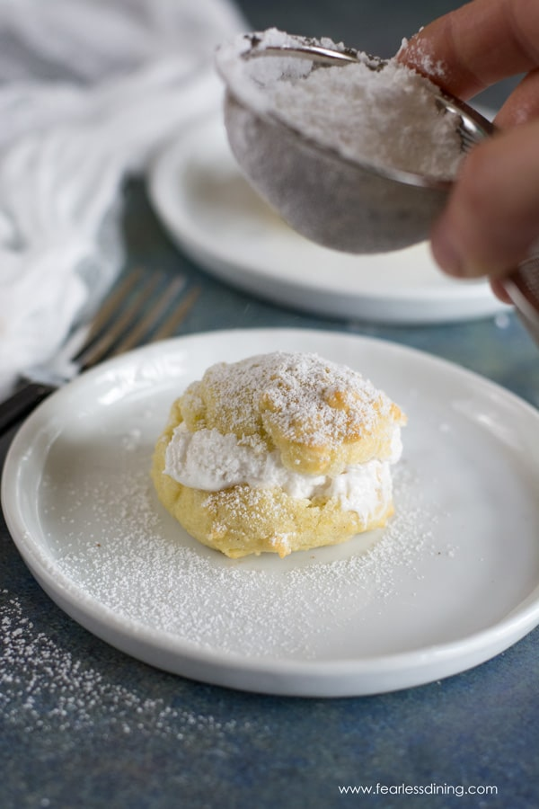 dusting powdered sugar on top of the gluten free cream puff