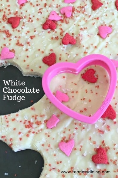 a cookie cutter cutting out heart shaped fudge for Valentine's Day