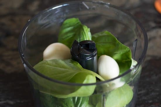 Fresh basil and garlic cloves in a cuisinart