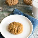 a gluten free molasses cookie on a plate next to a rack of cookies