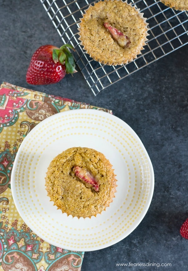 a paleo strawberry muffin on a plate. A napkin is under the plate and the rack of muffins is behind the plate.