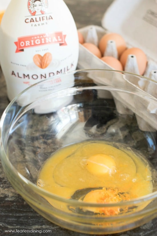 eggs, orange juice and orange zest in a bowl with almond milk and an egg carton in the background