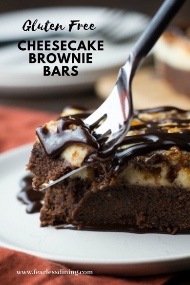 A fork digging into a gluten free cheesecake brownie bar