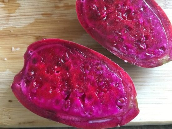 hot pink prickly pear fruit, cut in half on a cutting board