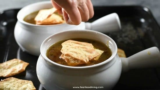 adding crackers to the soup