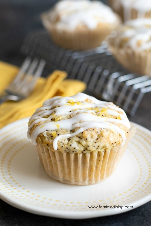 a gluten free lemon poppy seed muffin on a white plate. The muffin is topped with a lemonade icing.