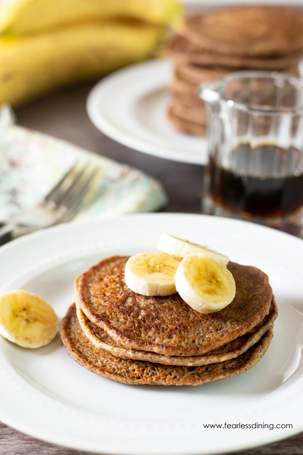 A plate with three banana pancakes stacked on top. Sliced bananas are on top of the stack.