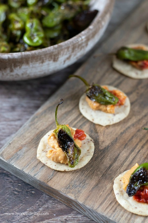 Padron pepper appetizer. The peppers are on top of crackers with roasted red pepper hummus.