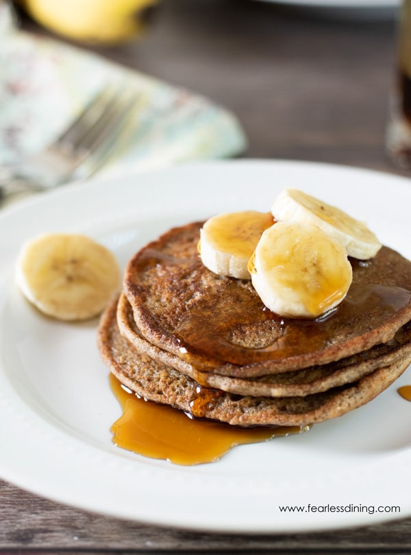 a stack of banana pancakes with syrup running down the side of the stack onto the plate.