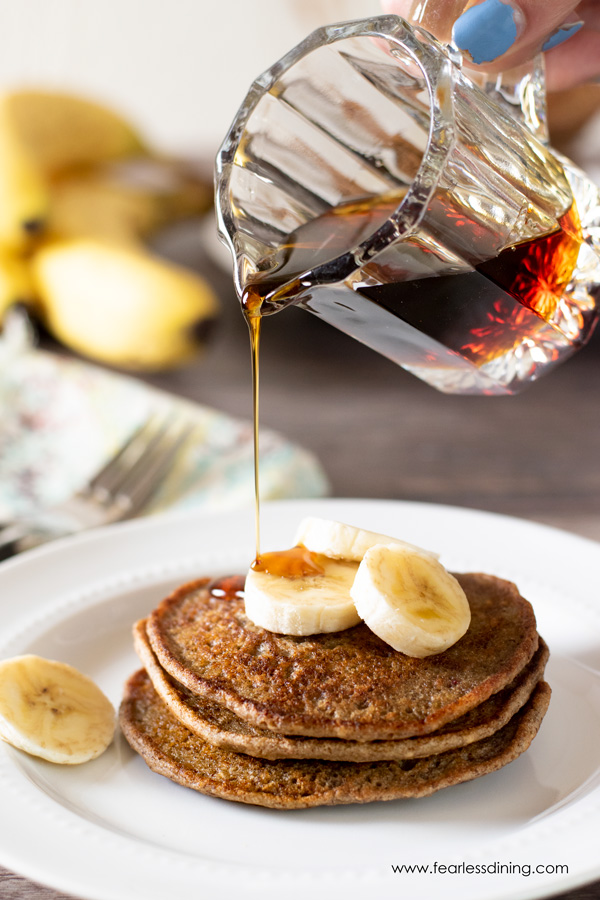 pouring syrup onto a stack of pancakes with sliced bananas on top.