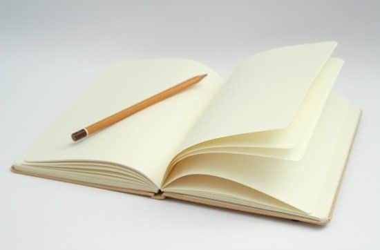 an open blank notebook with a pencil on a page
