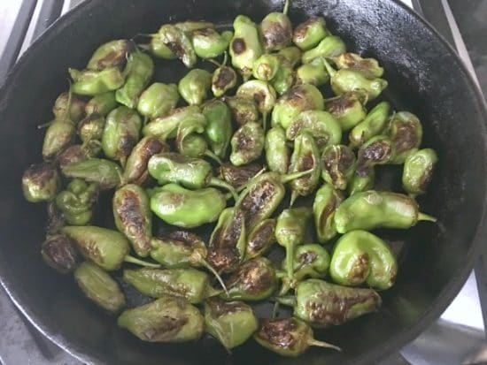 Cooking padron peppers in a cast iron pan over high heat.