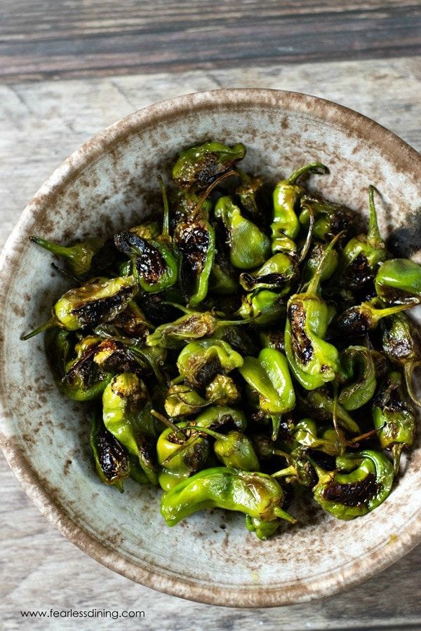 roasted padron peppers in a pottery bowl