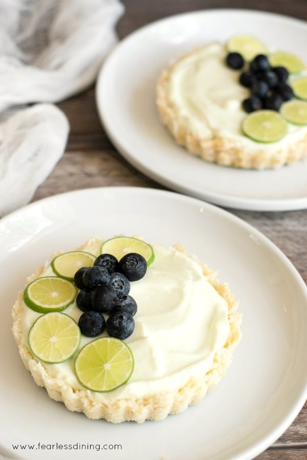 A gluten free fruit tart with key lime slices and fresh blueberries on a white plate.