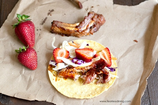 a taco made with bbq pork rib meat. The taco is on a piece of brown paper with a rib and strawberries in the background.