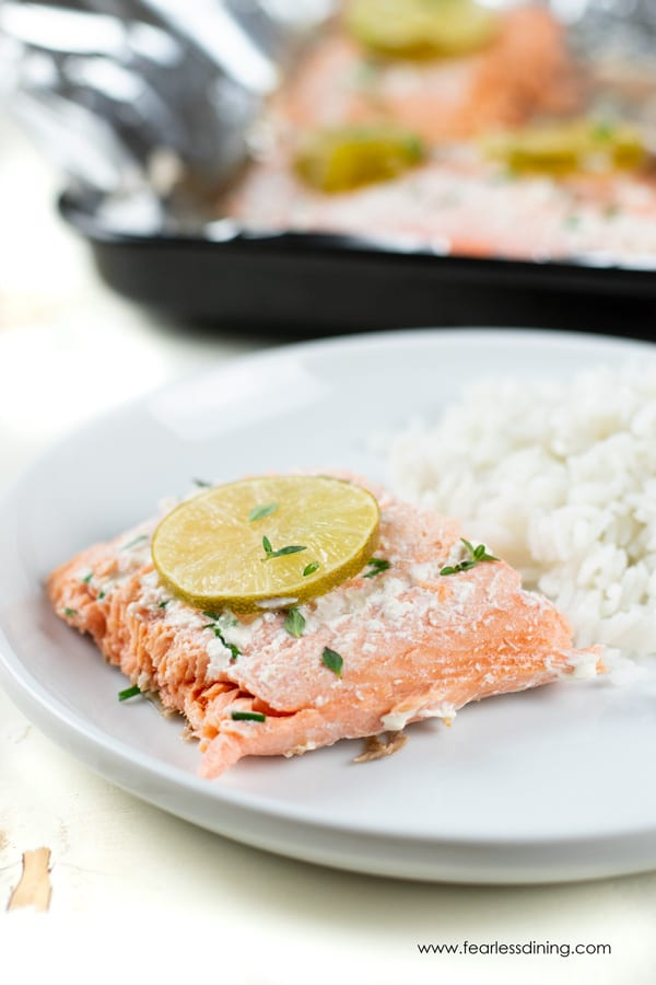 a piece of wild salmon on a plate with a lime garnish and white rice.