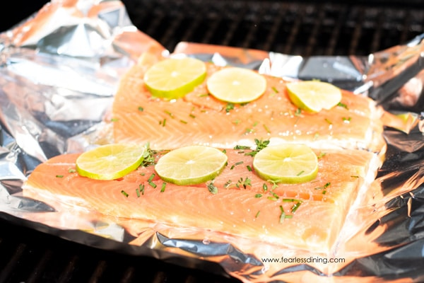 two pieces of salmon on aluminum foil on the grill
