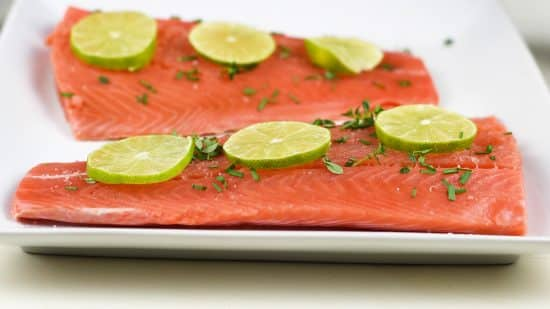 raw salmon topped with fresh herbs and lime slices on a plate