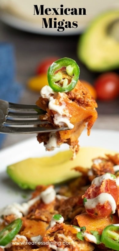 a fork holding up a bite of migas. A sliced jalapeño is on top
