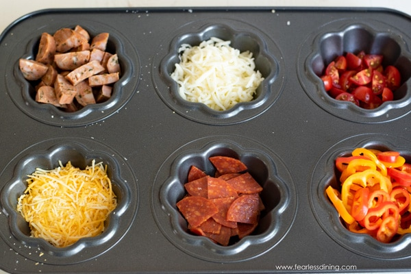 a muffin tin with sausage, cheese, and other toppings for an egg muffin